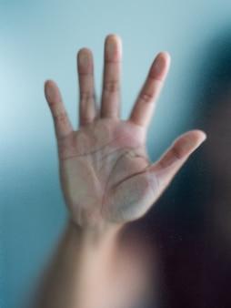 Mano borrosa de la mujer detrás del pánico de vidrio esmerilado, pánico y negativo oscuro emocional