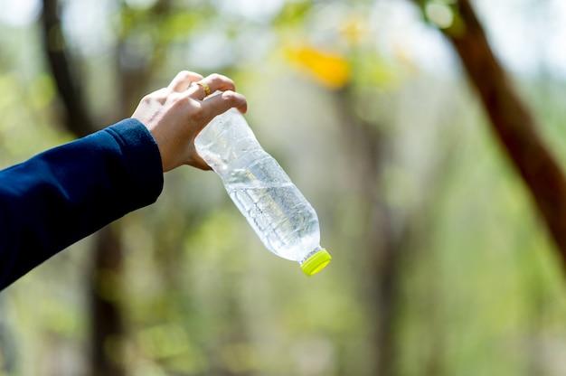 Mano y botella de agua. agua potable.