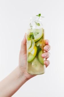 Mano con botella de fruta limonada.
