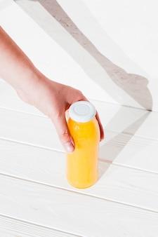 Mano con botella de zumo de naranja.