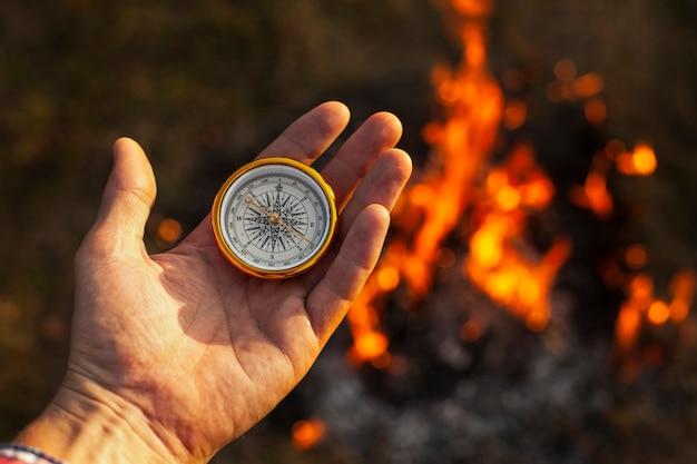 Mano con brújula y llamas de fuego a lo largo
