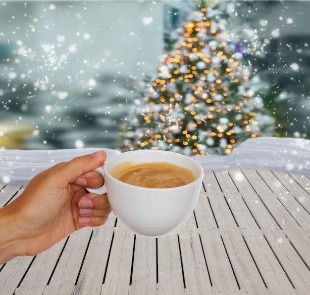 Mano con café de invierno, navidad con nieve en segundo plano.