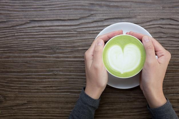 Mano con café con leche verde sobre fondo de madera