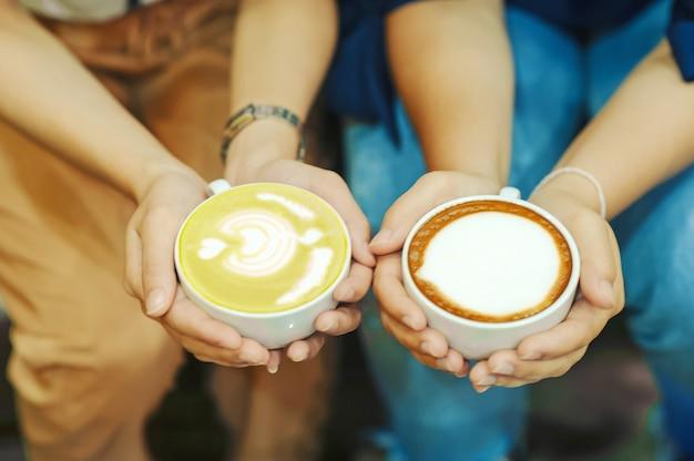 Mano y café y té verde caliente a los jóvenes les encanta tomar bebidas calientes.