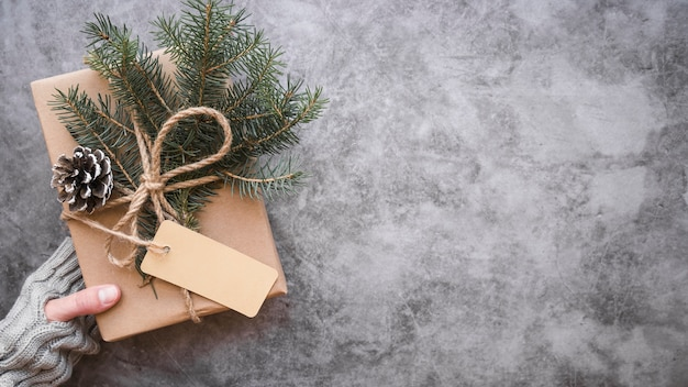Mano con caja de regalo decorada con gancho, etiqueta y ramitas de abeto