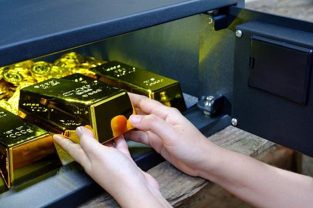 Mano caja de seguridad de acero electrónica abierta llena de pila de monedas y barra de oro