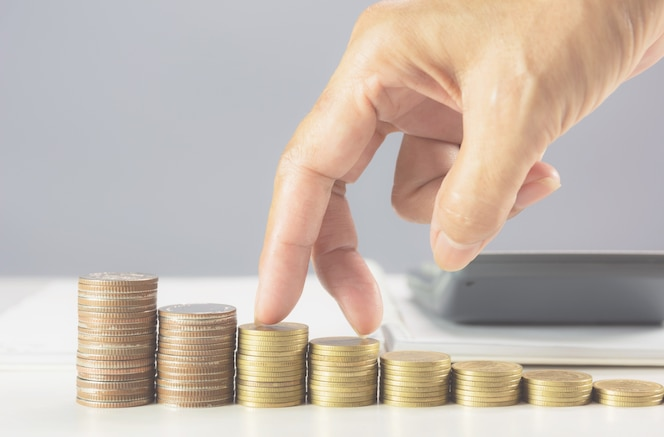 Mano caminando sobre la pila de monedas sobre la mesa. concepto de negocio financiero y creciente.