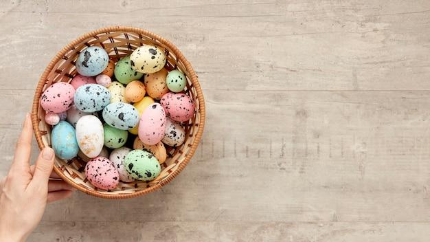 De la mano con la canasta llena de huevos para pascua