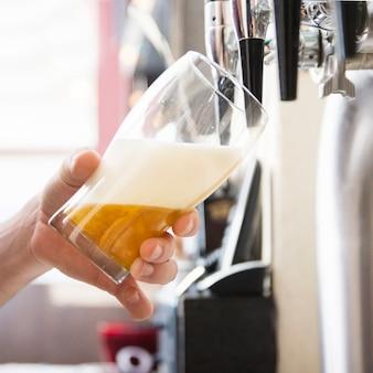 Mano del cantinero que vierte una cerveza de cerveza dorada grande en golpecito