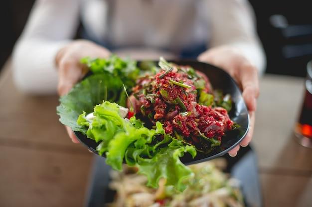 Mano y carne fresca, comida de personas que les gusta comer carne fresca, comida cruda