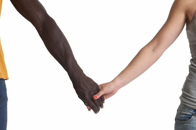Una mano caucásica y una africana sobre fondo blanco