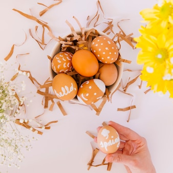 Mano cerca de conjunto de huevos de pascua naranja en un tazón entre flores