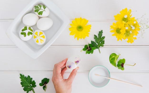 Mano cerca de los huevos de pascua en el recipiente, flores, hojas y taza con líquido tinte