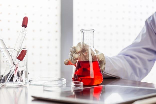 Mano de científico sosteniendo el matraz con dejar caer líquido químico sobre la mesa