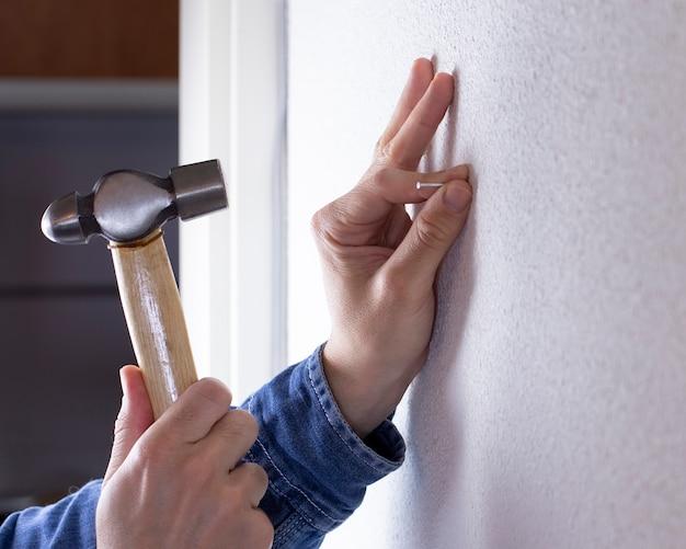 Mano clavando un clavo en la pared con un martillo
