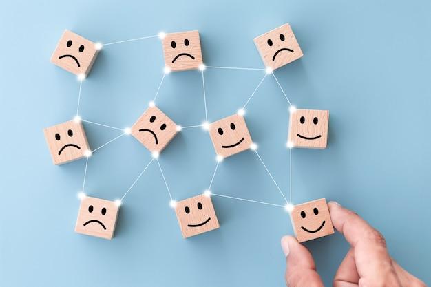Mano del cliente elegir cara sonriente en cubo de madera