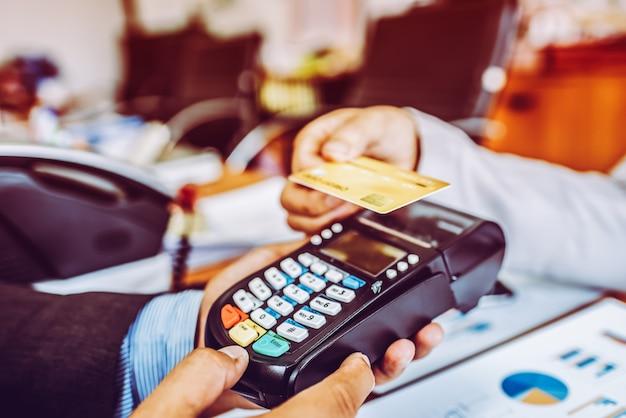 Mano del cliente del hombre de negocios que paga con la tarjeta de crédito sin contacto de la tecnología de nfc.