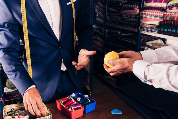 La mano del cliente mostrando una bola de lana amarilla a un diseñador de moda masculino en la tienda