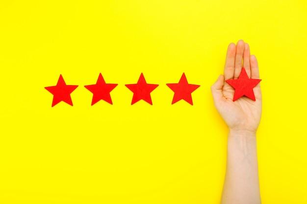 Mano del cliente muestra el símbolo de cinco estrellas clasificación de servicio sobre fondo amarillo