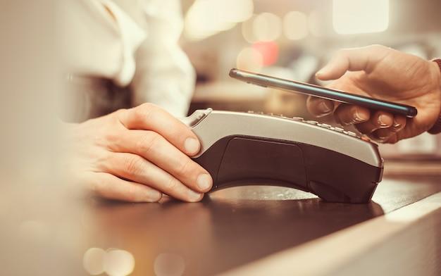 La mano del cliente paga con el teléfono inteligente en la tienda con tecnología nfc
