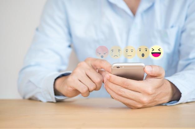 Mano del cliente tocando el teléfono móvil para enviar una evaluación de servicio al cliente