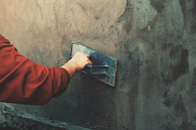 Mano de closup de los trabajadores enyesados en la pared al aire libre en el sitio de construcción