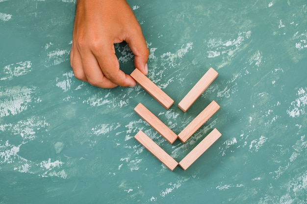 Mano colocando bloques de madera