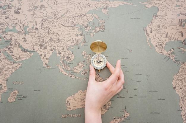 Mano colocando una brújula sobre un mapa del mundo