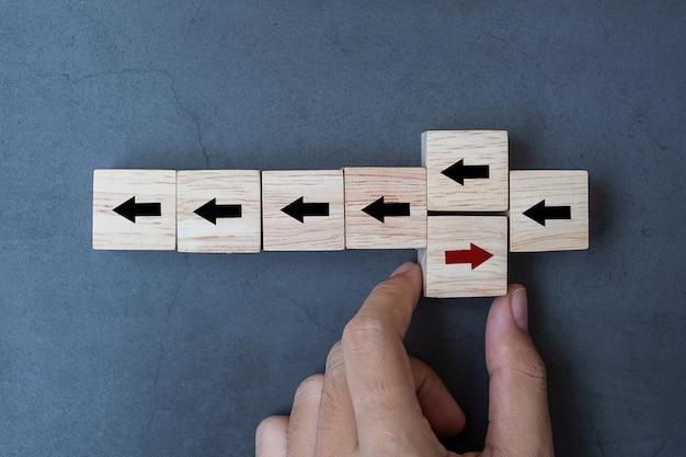 Mano colocando flecha roja bloque de madera