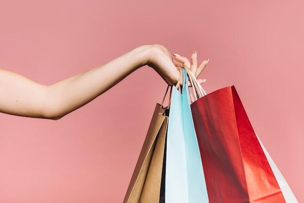 Mano con coloridas bolsas de la compra.