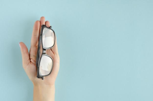 Mano con composición de anteojos sobre fondo azul.