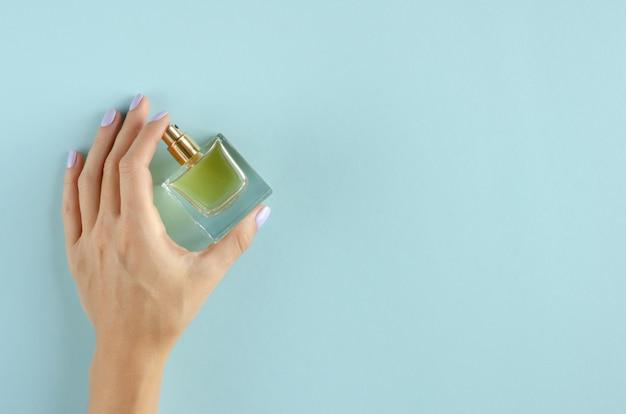 Mano con la composición de la botella de perfume en fondo azul.