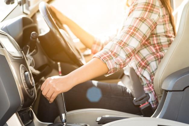 Mano del conductor de la mujer cambiar o cambiar la palanca de cambios y conducir un automóvil
