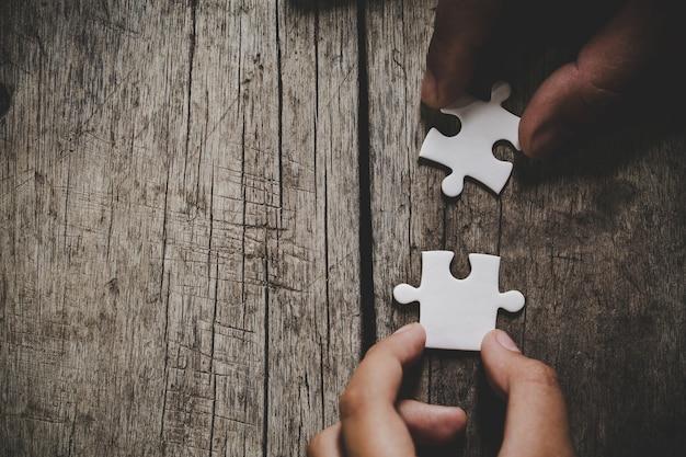 Mano conectando piezas del rompecabezas en la mesa