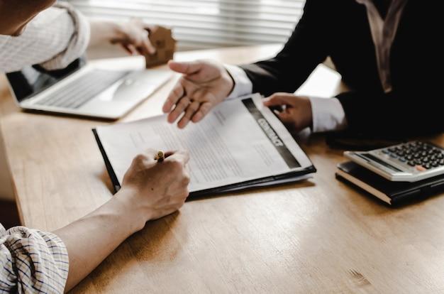 Mano del contrato de firma del cliente del hombre joven para comprar casa con el agente inmobiliario