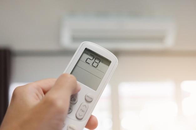 Mano con control remoto dirigido al aire acondicionado dentro de la habitación