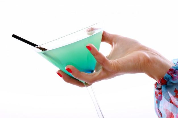 De la mano con una copa de cóctel