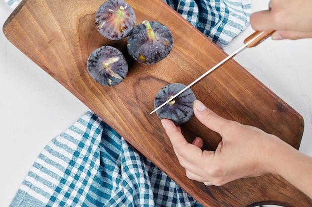 Mano cortando un higo sobre una tabla de cortar de madera con un mantel azul.