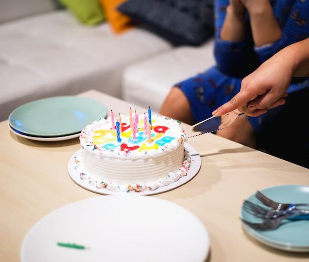 Mano cortando pastel de cumpleaños