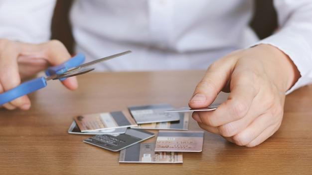Mano de corte de tarjetas de crédito con tijeras en la mesa