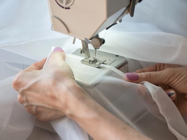 La mano cose un tul en la máquina de coser.