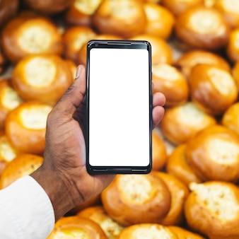 Mano de la cosecha con el teléfono inteligente en el fondo de pastelería