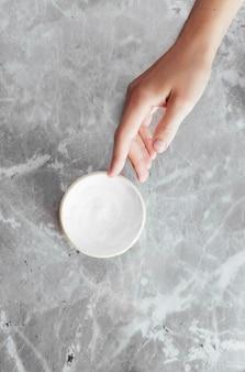 Mano y crema sobre fondo de mármol