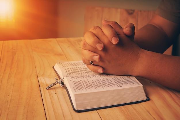 Mano cristiana mientras reza y adora por la religión cristiana