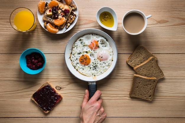 Mano de cultivo poniendo huevos fritos cerca de la comida del desayuno