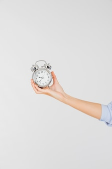 Mano de cultivo con reloj despertador