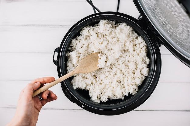 Mano de cultivo tomando arroz del vapor