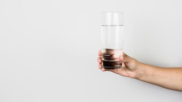 Mano de cultivo con vaso de agua