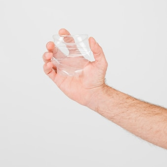 Mano de cultivo con vaso de plástico