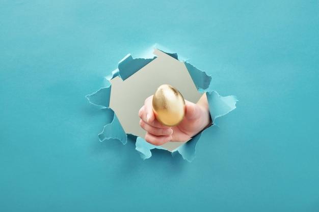 Mano da huevo de oro a través del orificio de papel